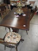 A dark oak draw leaf table and 4 Ercol chairs.