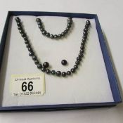 A black pearl necklace, bracelet and earrings.