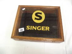 A table top display cabinet with Singer advertising