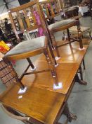 A 1950's oak draw leaf table with 4 chairs.
