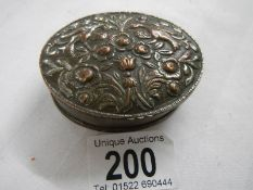 An old silver plate on copper snuff box with embellished top.