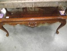 A dark wood stained carved long coffee table with glass top.