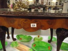 A dark wood nest of 3 tables with glass tops.