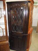 A dark oak linen fold lead glazed corner cabinet.