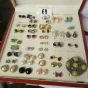 A case containing approximately 34 pairs of earrings including turquoise and pearl.