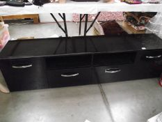 A long low black sideboard with drawers and cupboards.