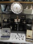 4 shelves of assorted chrome and silver plate including cutlery, tray, condiment sets etc.