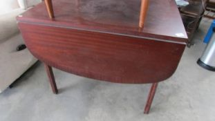 A teak drop leaf table.