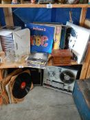 An old tape recorder and 2 shelves of records.