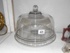 A large heavy clear glass cake dome on foot