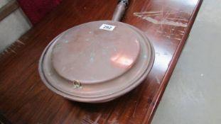 A copper warming pan.