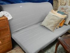 A futon with dark blue cover and cushions.