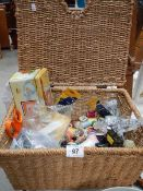 A wicker basket containing sewing items.