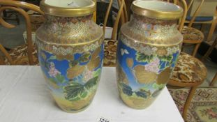 A pair of hand painted Chinese vases.