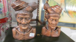 A pair of carved wood male and female busts.