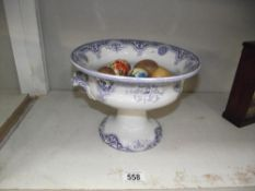 A raised blue and white pottery bowl containing a collection of pottery and wooden eggs.