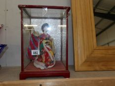 A Japanese doll in glass case (case complete but needs attention).
