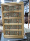 A small cane 5 drawer chest of drawers