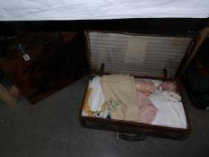 A vintage case containing various household textiles and linens including napkins,
