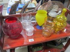 A shelf of various coloured glass etc