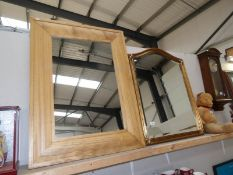 A large gilt framed mirror and a large wood framed mirror.
