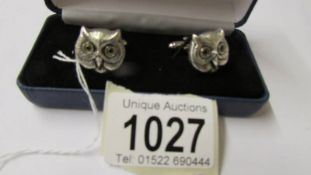 A pair of silver owl cuff links with glass eyes.