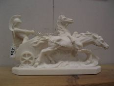 A white statue of a chariot with charioteer and two horses