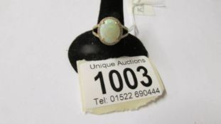 A 14k gold ring set small diamonds and central opal (approx. 10mm x 12mm), size N.