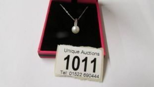 A white gold diamond pendant necklace with cultured pearl drop.