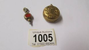 A 19th century yellow metal sovereign case and a small watch key.