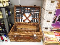 A picnic basket with contents and a 4 drawer wicker chest.