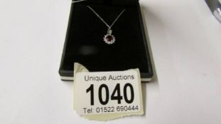 An 18ct white gold ruby and diamond pendant necklace, 90 points, cased.