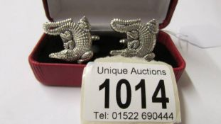 A pair of silver alligator style cuff links.