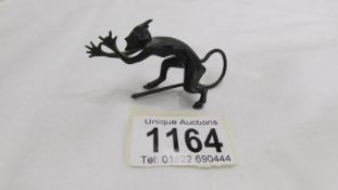 A miniature bronze figure of Satan.