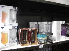 A shelf of boxed sets of drinking glasses.