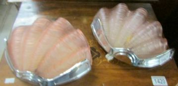 A pair of pink glass clam shell wall lights.