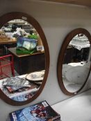 A pair of oval retro mounted mirrors