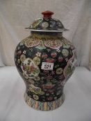 A large oriental lidded pottery urn.