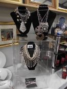 A display cabinet (plastic) and a quantity of costume jewellery on stands