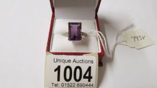 A 9ct gold ring set large emerald cut amethyst and with diamond set shoulders,