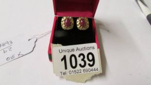 A pair of yellow gold ruby and diamond cluster earrings with screw backs.