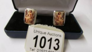 A pair of silver and enamel set cuff links with nude images.