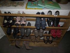 A wooden shoe rack and quantity of ladies shoes.