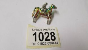 A silver and plique a jour horse and rider brooch/pendant.