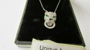 A silver adn CZ Cartier style panther pendant necklace with emerald cultured eyes.