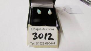 A pair of pear shaped opal stud earrings.