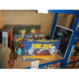 A large shelf of Star Trek collectables including Jigsaw puzzles, VHS, diecast etc.