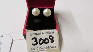 A pair of freshwater pearl stud earrings on silver posts.