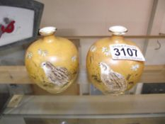 A pair of signed oriental pomegranate vases hand painted with birds, both a/f.