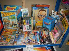 A large shelf of Thunderbird books, magazines, videos, posters etc.